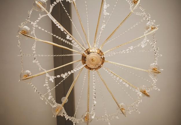 宮殿の天井の下にぶら下がっている豪華な高価なシャンデリア。豊かなマナーハウスにある豪華なクリスタルシャンデリア。