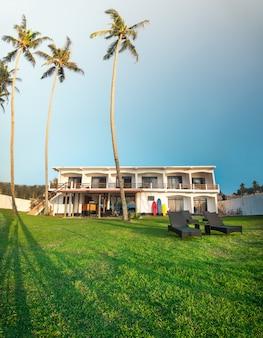 스리랑카의 코코넛 나무가 있는 푸른 잔디밭에 있는 고급스러운 외관 디자인 호텔 빌라
