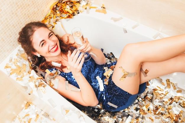 高級ファッションスタイルの誕生日パーティー。シャンパンとガラスを保持し、バスタブに横たわってドレスを着た高級ブルネットの女の子。周りの紙吹雪。