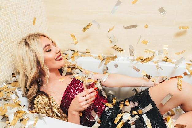 高級ファッションスタイルのお祝い。バスタブに横たわって、笑顔で、シャンパンでガラスを保持している高級ブロンドの女の子。周りの紙吹雪。