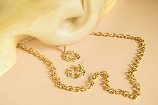 Luxury gold jewelry chain and earrings on pink background with silk