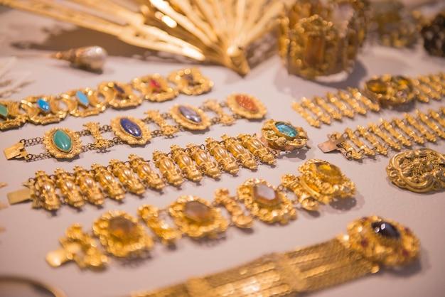 高級ゴールドジュエリー光沢のあるゴールドブレスレットとハンドヘルドファンさまざまな美しいアンティークジュエリー
