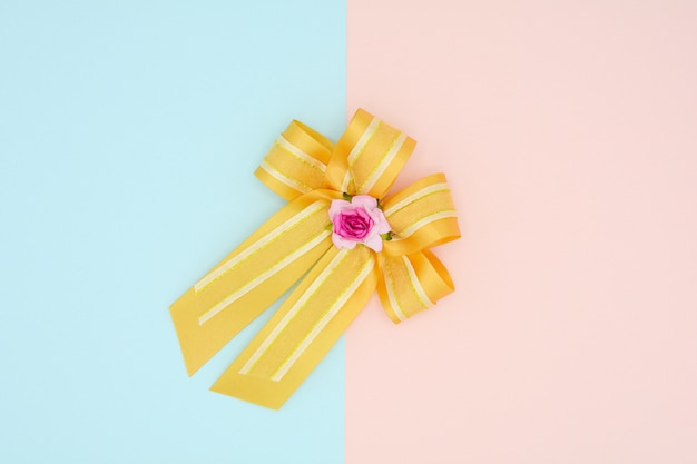 Luxury gold satin ribbon on pink and blue background