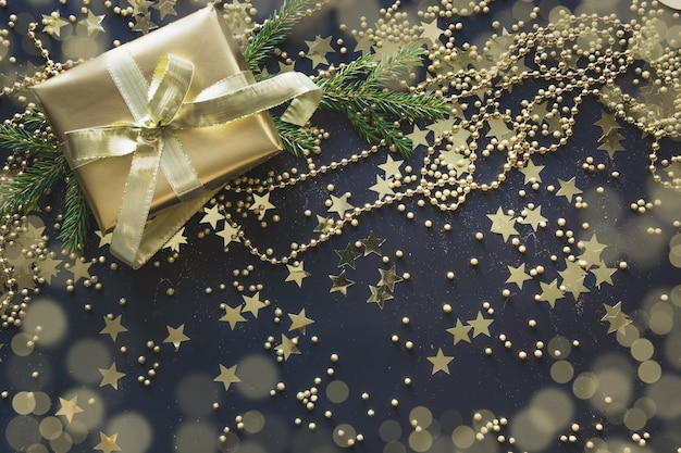Luxury golden gift box with gold ribbon on shine black . christmas. flat lay. top view. festive backdrop. xmas pattern. .