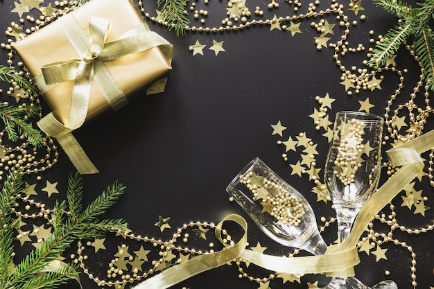 Luxury golden gift box with two glass champagne on black backgroud christmas party flat lay view from above. xmas.