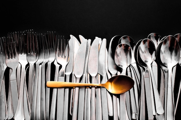 A luxury golden spoon stands out from the rest of the simpler and cheaper cutlery, isolated on a black background with copy space.