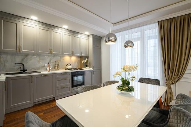 Роскошный серый и белый современный классический интерьер кухни с обеденным столом выполнен в современном стиле