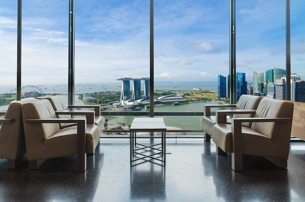 Luxury hotel lounge with windows overlooking city in singapore.