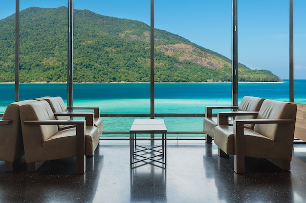 Luxury hotel lounge with windows overlooking sea in phuket, thailand.