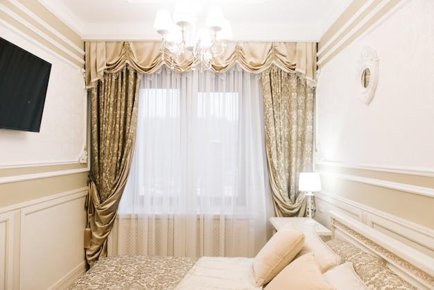 ダブルベッドと明るいインテリアの高級ホテルの部屋