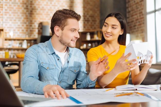Роскошный дом. два оптимистичных жизнерадостных коллеги мужского и женского пола придумывают план, обсуждая и работая вместе
