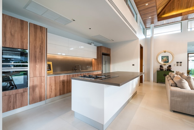 Luxury interior design pool villa in kitchen area which feature island counter, built in f