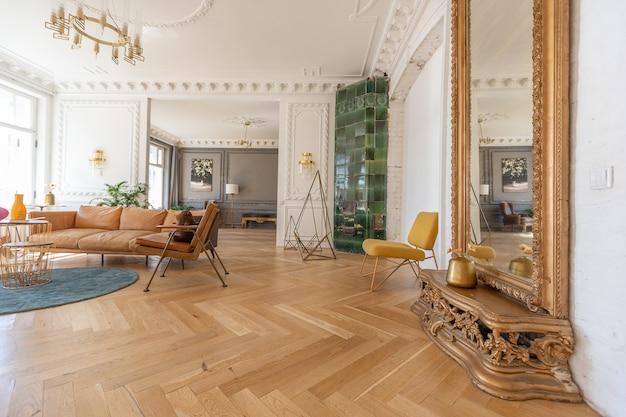 현대적인 가구를 갖춘 오래된 19세기 유서 깊은 집에 있는 넓은 아파트의 고급스러운 인테리어입니다. 높은 천장과 벽은 치장 벽토로 장식되어 있습니다.
