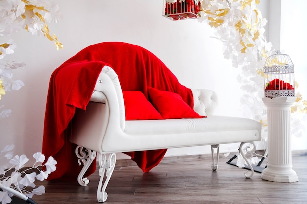 Luxury interior in white and red with sofa, bird cage with red roses. expensive decor arrangements