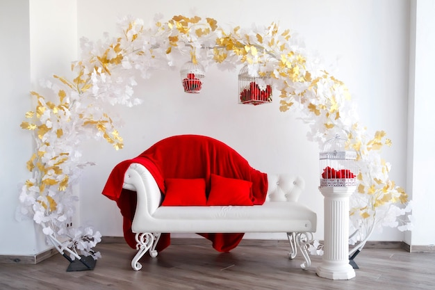 Luxury interior in white and red with sofa, bird cage with red roses