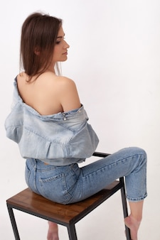 優雅に回転するバースツールに座って背中と肩を開いたシャツを着た豪華な女性。ブルージーンズのゴージャスなロングレッグ