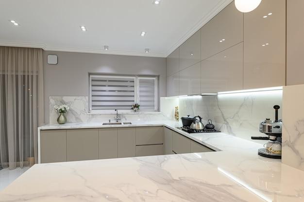 ダイニングルームと一体となった豪華でモダンな白い大理石のキッチン