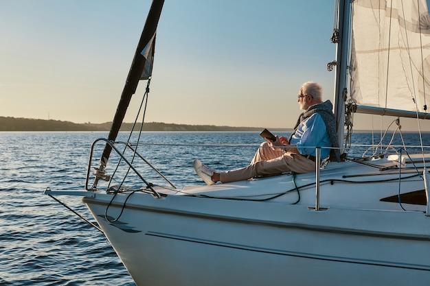 Роскошный образ жизни, вид сбоку расслабленного пожилого мужчины, сидящего на борту парусной лодки или яхты