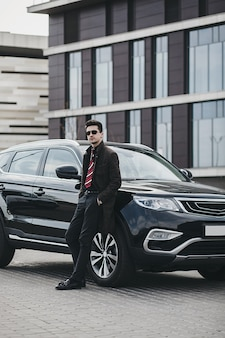 Роскошный образ жизни. красивый молодой человек в деловой одежде стоит возле своей машины