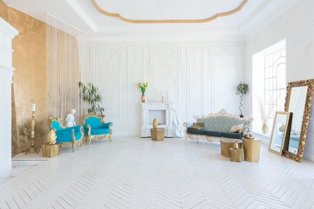 Luxury light interior of living room with gold wall and chic expensive furniture in white and gold colors