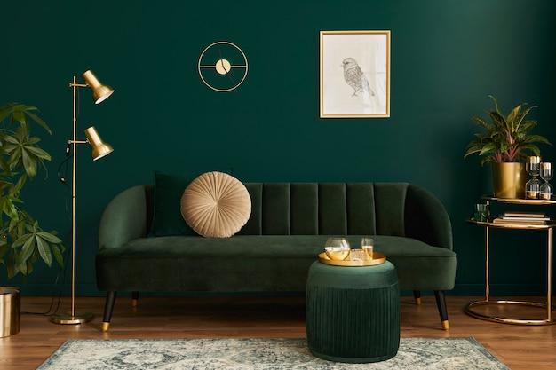 Роскошная гостиная в доме с современным дизайном интерьера, зеленый бархатный диван, журнальный столик, пуф, золотая отделка, растение, лампа, ковер, макет рамки для плаката и элегантные аксессуары. шаблон.