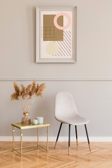 Luxury living room interior with elegant green armchair, gray stand and chic accessories. mock up paintings frame on the molding gray wall in stylish home decor. template.