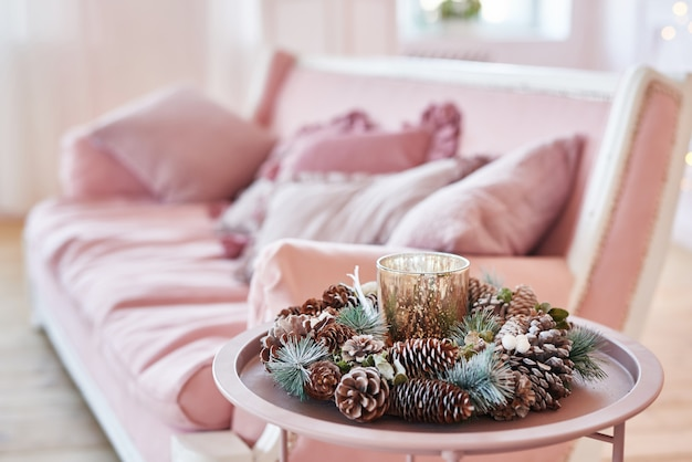 Luxury living room interior with sofa decorated chic christmas tree, gifts and pillows. classic interior in pink shades. christmas at home