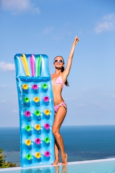 Luxury living, vacation style summer portrait of happy young woman with tanned slim fit body, having sun at luxury villa, holding air mattresses on her hands.