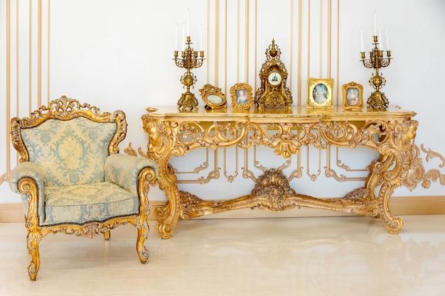 황금 가구 세부 사항과 밝은 색상의 고급 거실. 우아한 클래식 인테리어