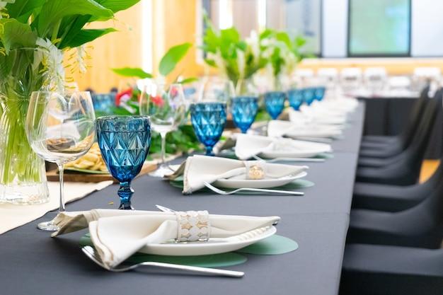 긴 테이블 패턴에 꽃 장식이있는 검은 색 커버 테이블이있는 고급 점심 또는 저녁 식사 세트.