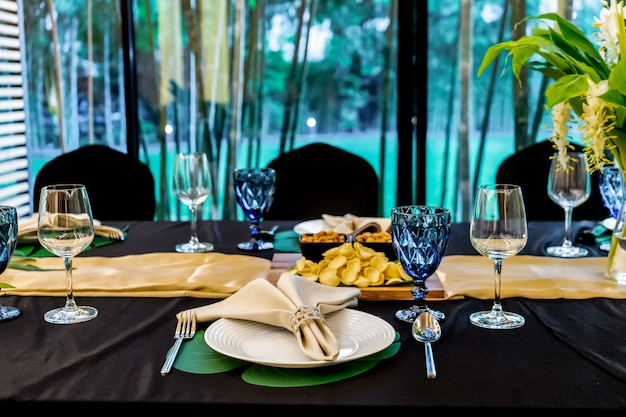 花の装飾が施された黒いカバーテーブルを備えた長いテーブルパターンにセットされた豪華なランチまたはディナー。