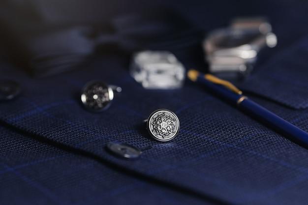 Luxury men cufflinks, accessories and pen over suit background
