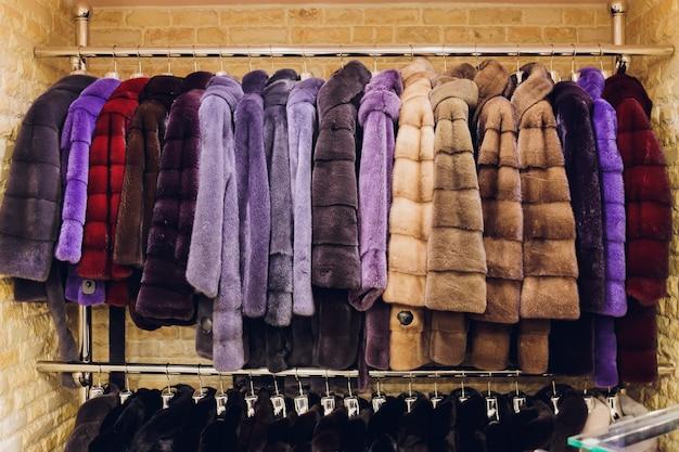 高級ミンクコート。市場のショーケースにあるグレー、ブラウン、パールカラーの毛皮のコート