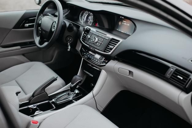 Роскошный современный интерьер автомобиля. рулевое колесо, рычаг переключения передач и панель приборов. деталь интерьера современного автомобиля. автоматическая ручка переключения передач.
