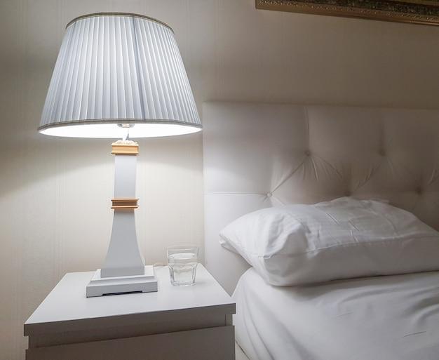 침대 옆 탁자와 야간 조명, 베개가 있는 밝은 침실의 고급스럽고 현대적인 디자인, 침대 준비, 물 한 잔.