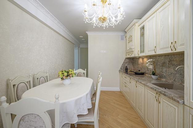 Роскошный современный неоклассический бежевый кухонный интерьер с шкафчиком и обеденным столом