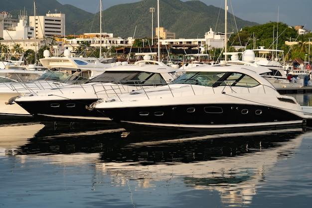 Роскошные моторные лодки и парусники пришвартованы в пристани для яхт на фоне гор.