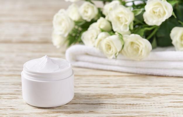 나무 테이블에 수건이 있는 흰색 플라스틱 항아리에 있는 고급 천연 얼굴 스킨케어 제품. 나무 테이블에 민감한 피부 크림의 플라스틱 흰색 항아리.
