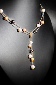 黒の背景に白、金、ライラックパールで作られた豪華なネックレス