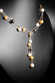 Luxury necklace made of white, gold and lilac pearls on a black background
