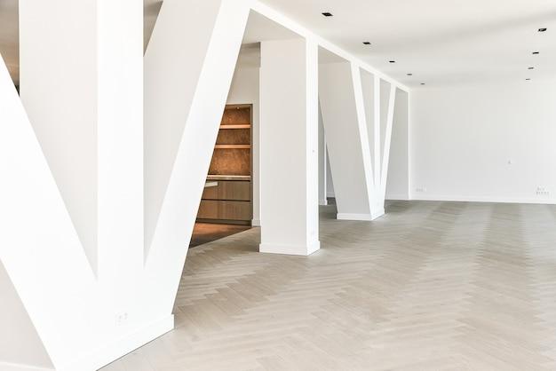 寄木細工の床と白い色の列の列を持つ豪華なオープンプランのペントハウスアパートメント