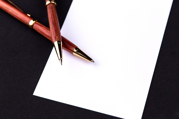 Luxury pen and mechanical pencil in wood and gold with a white sheet of paper