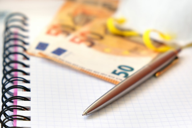 Роскошная ручка, защитная маска и банкноты 50 евро на белой тетради