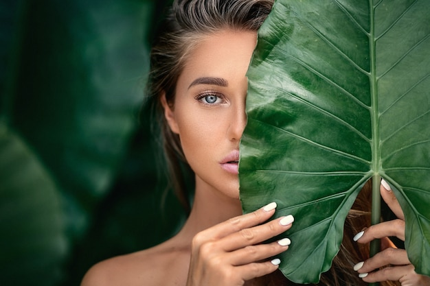 Luxury portrait of a beautiful young woman with natural makeup holds a big green leaf on blurred green