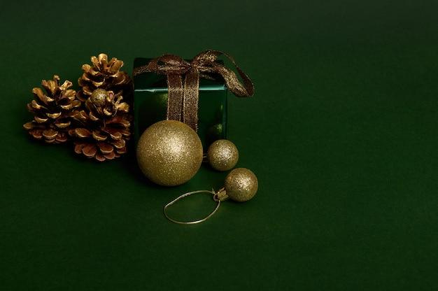 Роскошный подарок в блестящей зеленой подарочной упаковке с блестками, золотой лентой и золотым бантом, сосновыми шишками и сферическими елочными игрушками, выложенными на темном фоне. скопируйте место для рекламы