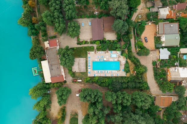 Luxury real estate on the shore of a azure pond top view drone shot