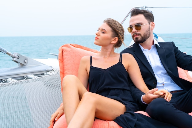 Luxury relaxing couple in nice dress and suite sits on bean bag in part of cruise yacht