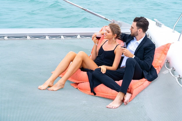 Luxury relaxing couple traveler in nice dress and suite sit on bean bag and drink a glass of wine in part of cruise yacht.