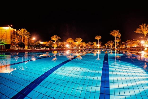 Роскошь, курортный бассейн, пальмы, гостиничные дома в идиллической ночи, световое освещение и отражение в чистой голубой поверхности воды на фоне темного неба. велнес и спа