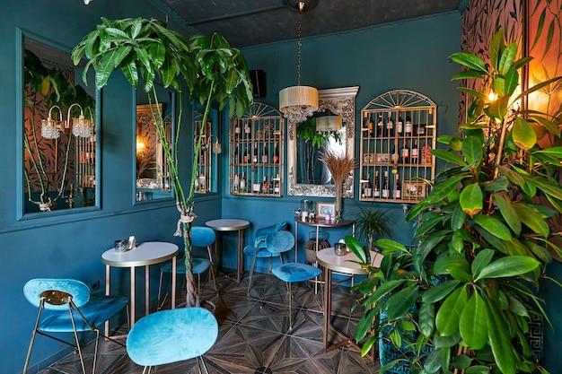 Роскошный интерьер ресторана в синих тонах с большим количеством растительности